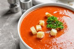 Bowl with fresh homemade tomato soup on table. Closeup royalty free stock image