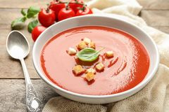 Bowl with fresh homemade tomato soup. On wooden table royalty free stock image
