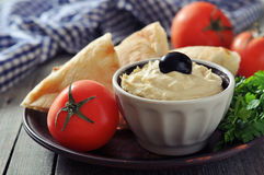 Bowl of fresh hummus. With olive and bread slices on wooden background Royalty Free Stock Images