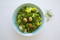 Bowl of fresh leafy green salad with olives, dill, onion and paprika. On the white table, healthy eating, diet, salad portion Royalty Free Stock Photos