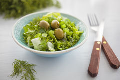Bowl of fresh leafy green salad with olives, dill, onion and paprika. On the white table, healthy eating, diet, salad portion Stock Photo