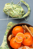Bowl of fresh mandarins with ball of thread and knitting needle on gray background Stock Photo