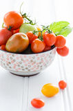Bowl of fresh mixed tomatoes. Arrangement of a variety tomatos in a bowl, cherry, roma, green, yellow, vine ripened with fresh green leaves Royalty Free Stock Photos