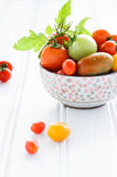 Bowl of fresh mixed tomatoes. Arrangement of a variety tomatos in a bowl, cherry, roma, green, yellow, vine ripened with fresh green leaves Stock Photo
