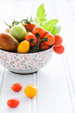 Bowl of fresh mixed tomatoes. Raw mixed tomatos in an ornate bowl, cherry, roma, green, yellow, vine ripened with fresh green leaves Royalty Free Stock Photos