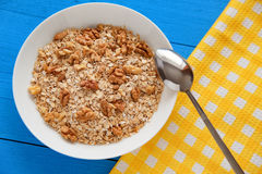 Bowl of fresh oatmeal walnuts on teal rustic table, hot and healthy food for Breakfast. Bowl of fresh oatmeal walnuts and kitchen towel on teal rustic table, hot Stock Photo