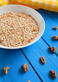 Bowl of fresh oatmeal walnuts on teal rustic table, hot and healthy food for Breakfast. Bowl of fresh oatmeal walnuts and kitchen towel on teal rustic table, hot Stock Images