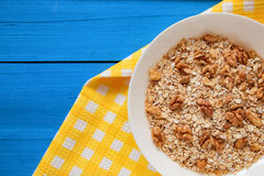 Bowl of fresh oatmeal walnuts on teal rustic table, hot and healthy food for Breakfast. Bowl of fresh oatmeal walnuts and kitchen towel on teal rustic table, hot Royalty Free Stock Image