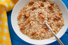 Bowl of fresh oatmeal walnuts on teal rustic table, hot and healthy food for Breakfast. Bowl of fresh oatmeal walnuts and kitchen towel on teal rustic table, hot Stock Image