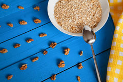 Bowl of fresh oatmeal walnuts on teal rustic table, hot and healthy food for Breakfast. Bowl of fresh oatmeal walnuts and kitchen towel on teal rustic table, hot Stock Photography