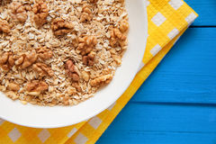 Bowl of fresh oatmeal walnuts on teal rustic table, hot and healthy food for Breakfast. Bowl of fresh oatmeal walnuts and kitchen towel on teal rustic table, hot Royalty Free Stock Images