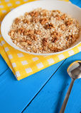 Bowl of fresh oatmeal walnuts on teal rustic table, hot and healthy food for Breakfast. Bowl of fresh oatmeal walnuts and kitchen towel on teal rustic table, hot Royalty Free Stock Photos