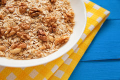 Bowl of fresh oatmeal walnuts on teal rustic table, hot and healthy food for Breakfast. Bowl of fresh oatmeal walnuts and kitchen towel on teal rustic table, hot Stock Photos