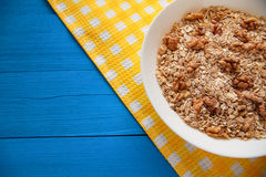 Bowl of fresh oatmeal walnuts on teal rustic table, hot and healthy food for Breakfast. Bowl of fresh oatmeal walnuts and kitchen towel on teal rustic table, hot Royalty Free Stock Photo