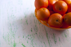 Bowl of fresh oranges. Dish with oranges stands on the old board Stock Photography