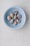 Bowl with fresh quail eggs on wooden background Stock Photography