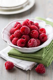 Bowl of fresh raspberries. Bowl of beautiful fresh raspberries on kitchen table Royalty Free Stock Photo