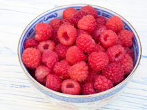 A bowl of fresh raspberries. Fresh raspberries in a blue china bowl, set on a white wooden board Stock Photo
