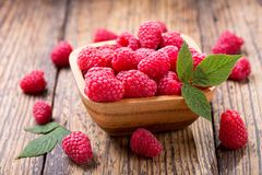 Bowl of fresh raspberries. On wooden table Stock Images
