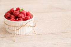 Bowl of fresh raspberries, mint leaf and natural jute twist. Bowl of fresh raspberries and mint leaf on wood board with natural jute twist Stock Photo