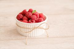 Bowl of fresh raspberries and mint leaf. On wooden board with natural jute twist. Tasty and sweet fruit Royalty Free Stock Photography