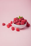 Bowl with fresh raspberries and mint leaves on a pink background. Copy space. Minimal concept.  Stock Image