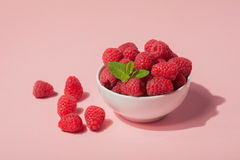 Bowl with fresh raspberries and mint leaves on a pink background. Copy space. Minimal concept. hard light Stock Photos