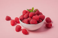 Bowl with fresh raspberries and mint leaves on a pink background. Minimal concept.  Royalty Free Stock Photo