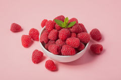 Bowl with fresh raspberries and mint leaves on a pink background. Minimal concept.  Stock Photography