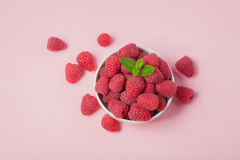 Bowl with fresh raspberries and mint leaves on a pink background. Top view Royalty Free Stock Image