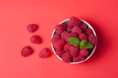 Bowl with fresh raspberries and mint leaves on a red background. Top view Royalty Free Stock Photos