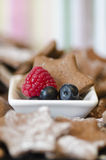 Bowl with fresh raspberry and blueberries. Bowl with fresh raspberry  blueberries and a tasty freshly baked star cookie in a traditional Christmas seasonal Royalty Free Stock Image