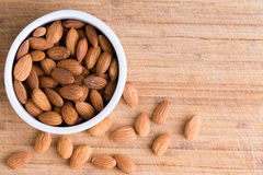 Bowl of fresh raw almonds on an old wooden board. Bowl of healthy fresh raw shelled almonds with some spilling out on an old wooden board with copy space viewed Stock Photo