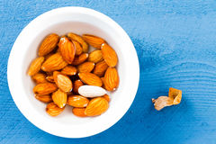 Bowl of fresh raw almonds with one peeled Stock Images