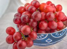 Bowl of fresh red grapes on white background. Fresh red grapes in the ceramic bowl Royalty Free Stock Photos