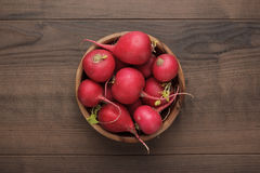 Bowl of fresh red radishes. Fresh red radishes in wooden bowl on the brown table Stock Image