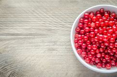 Bowl with fresh redcurrant on the wooden table Royalty Free Stock Photo