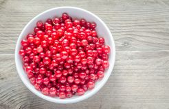 Bowl with fresh redcurrant on the wooden table Stock Photos