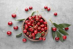 Bowl with fresh ripe cherries. On grey background Stock Image