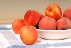 A bowl of fresh ripe peaches stock image