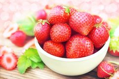 Bowl of fresh ripe sweet strawberries on berries and leaves background royalty free stock photography
