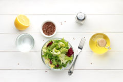 Bowl of fresh salad with flax seed, oil and lemon on wooden table. Royalty Free Stock Photos