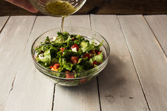 Bowl of fresh salad with salad dressing. Hand bowl of fresh salad with salad dressing royalty free stock image