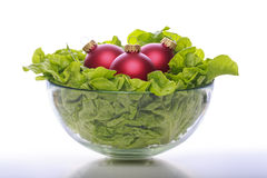 Bowl with fresh salad and three red christmas balls Stock Photography