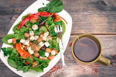 Bowl of fresh spinach and tomato salad with tea Stock Photography