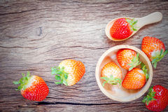 Bowl with fresh strawberries on an old wooden table. Stock Image