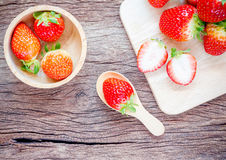 Bowl with fresh strawberries on an old wooden table. Stock Images