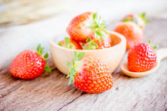 Bowl with fresh strawberries on an old wooden table. Royalty Free Stock Images