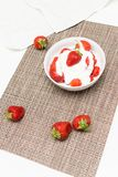 A bowl of fresh strawberries with sour cream and scattered berri. Es Stock Images