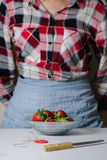 Bowl of fresh strawberries, woman standing at the table Royalty Free Stock Images